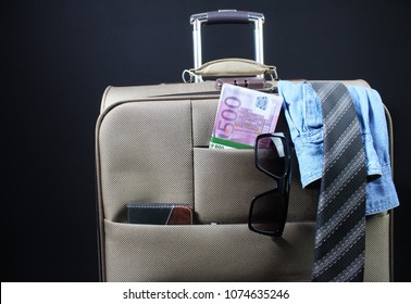 Photo of a travel suitcase packed with shirt, tie, money and sunglasses.