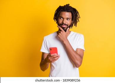 Photo of tricky influencer dark skin guy hold telephone look side sly eyes wear t-shirt isolated yellow color background