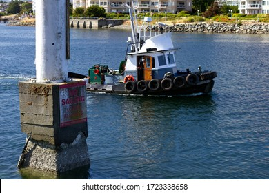 """Photo of a tugboat and a """"take down sails"""" sign in the bay near Victoria, Canada."""