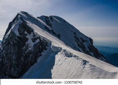 Photo of Turska Gora, Kamnik Savinja alps, Slovenia. High alpine peak and a sharp snow ridge leading to the summit. Blue sky, great outdoor day and adventure ascent in an alpine landscape.