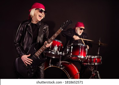 Photo of two aged pensioner lady man rock group perform concert play drum instruments solo guitar hobby bring money wear trendy rocker leather outfit bandana isolated black color background