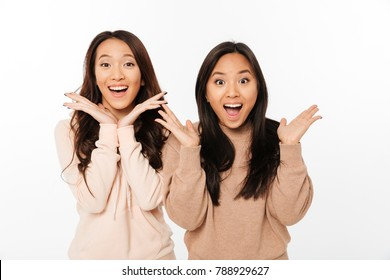 Photo of two asian pretty shocked ladies sisters standing isolated over white background. Looking camera.
