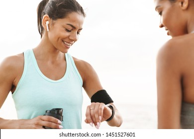 Photo of two attractive multiethnic sportswomen in tracksuits smiling and looking at wristwatch while standing over white wall outdoors