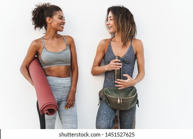 Photo of two attractive multiethnic sportswomen in tracksuits smiling and holding yoga mat while standing over white wall outdoors