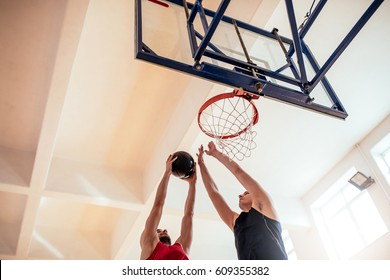 Photo of two basketball players slam dunking.