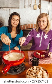 Photo of two beautiful women dipping bread into the melted cheese in a fondue pot.