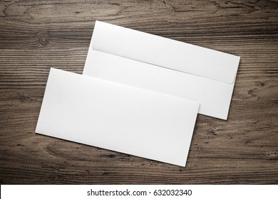 Photo of two blank envelopes on a dark wooden table background. Front and back side. Template for branding identity. Top view.