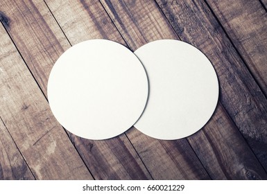 Photo of two blank white beer coasters and coffee beans on wood table background. Blank template for your design. Top view.