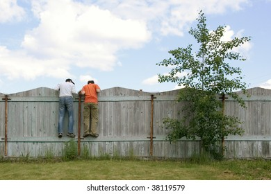 Photo of two boys on the fence looking for something