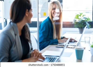 Photo of two business women looking at each other as they work with laptops at the divided desk in the coworking space. Concept of social distancing.