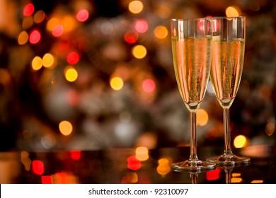 Foto von zwei Champagnerbrillen auf Glastisch mit Bokeh-Hintergrund