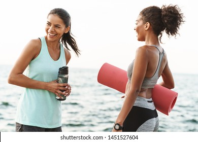 Photo of two cheerful multiethnic sportswomen in tracksuits talking and laughing while standing with yoga mat by seaside in morning