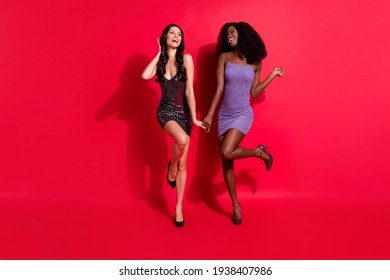 Photo of two chic lovely cute ladies hold hands dance have fun wear short dress stilettos isolated red color background
