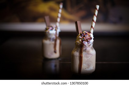 Photo of two chocolate shake jars with one in focus and one in background