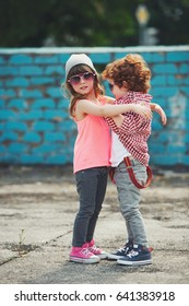 photo of two cute hipsters hugging outdoors