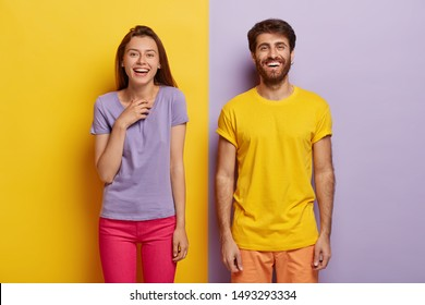 Foto von zwei begeisterten jungen Frauen und Männern stehen zusammen, drücken gute Emotionen aus, lächeln fröhlich, verbringen Freizeit zusammen, haben Spaß, posieren auf gelbem und violettem Hintergrund, beiläufig gekleidet