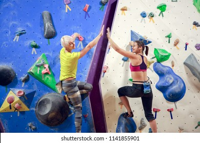 Photo of two female athletes making handshake on climbing wall in sports hall