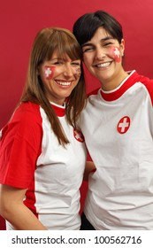 Photo of two female Swiss sports fans smiling and cheering for their team.