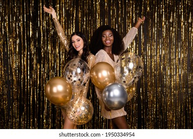 Photo of two festive ladies hold air balloons look camera raise hands wear glossy short dresses isolated tinsel background