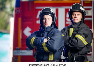 Photo of two firemen with hands on waist near fire engine