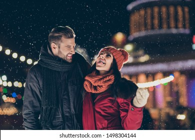 Photo of two funny people spend x-mas evening together playful good mood catching snowflakes by tongue wearing warm coats outdoors