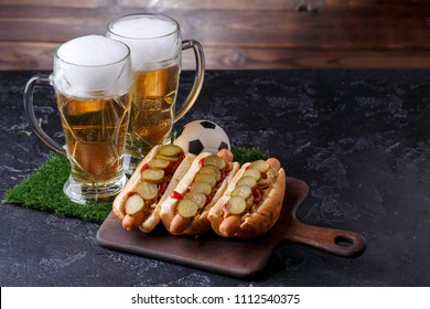 Photo of two glasses of beer, hot dogs, soccer ball