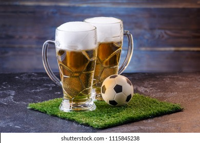 Photo of two glasses of beer, soccer ball on green grass