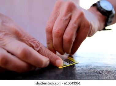 Photo of two hands scratching a scratch card with shallow focus.