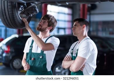 Photo of two handsome auto mechanics examining car wheel