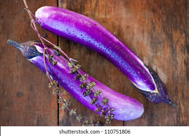 Photo of two Japanese  eggplants with water droplets on a wood table