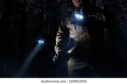 Photo of a two male person in brown tactical outfit jacket, gloves using knife and lighting up the way with head flashlights on night woods background.