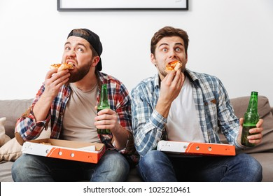 Photo of two manly men in casual shirts eating pizza and drinking beer while watching football game at home