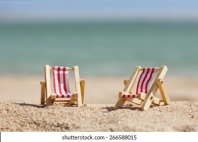 Photo Of Two Miniature Deckchairs On Sandy Beach