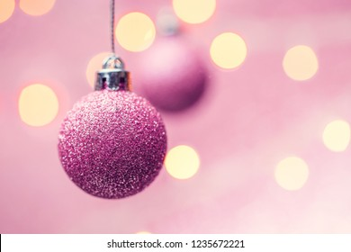 Photo of two New Year's pink balls on pink background with spots.
