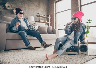 Photo of two people grandparent little granddaughter cool vintage style specs denim outfit hat house party sit on tape player recorder sing mic old fashion song stay home quarantine indoors