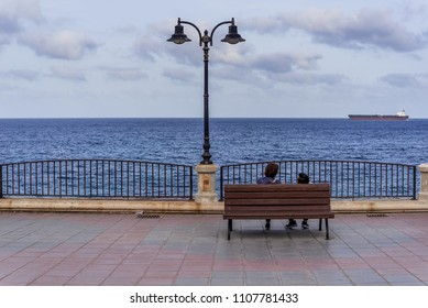 Photo of Two people sitting on bench and watching mediterranean sea, Valletta, Malta