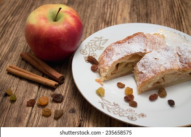 Photo of two portions of apple pie strudel on white plate with golden motif on old wooden board with cinnamon and raisins around and with one red apple near the plate.