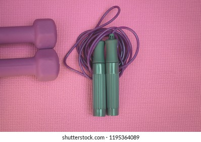photo of two purple weights and a skipping rope on a pink yoga mat