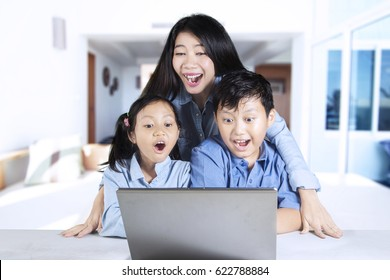 Photo of two shocked children and her mother, looking at a laptop screen. Shot at home