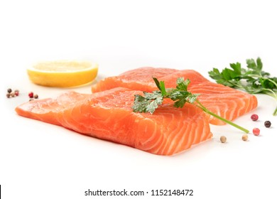 A photo of two slices of salmon with lemon, pepper, and parsley, on a white background with copy space. Selective focus
