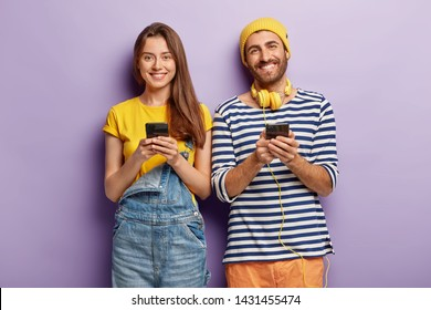 Photo of two smartphone geeks use modern technologies for posting new photos in social networks, connected to wireless internet check notification. Woman in overalls spends leisure time with boyfriend