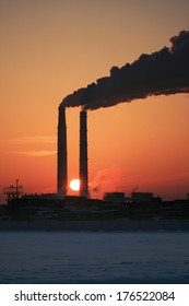 Photo of two smoking chimneys against the sun