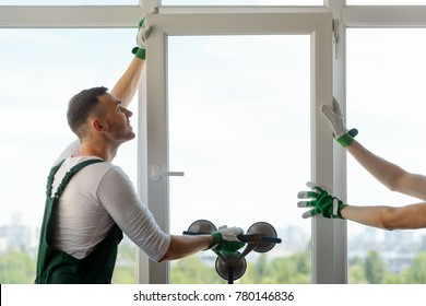 Photo of two workers installing a plastic window. Man holding a glass pane with a vacuum lifter.