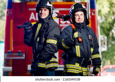 Photo of two young firemen with axes in hands near fire engine