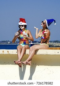 Photo of two young girls in Santa's hats having fun on the beach with shaving foam. Happy Christmas on vacation