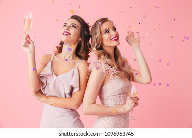 Photo of two young party women smiling and drinking champagne from glasses while standing under falling confetti isolated over pink background