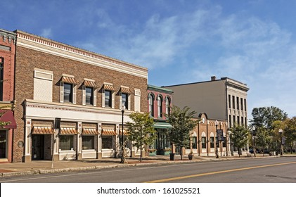 A photo of a typical small town main street in the United States of America. Features old brick buildings with specialty retail shops and restaurants. Decorated with autumn decor.