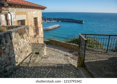 Photo of typical Spanish alleyway with sea, blue sky and sunlight