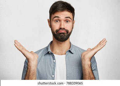 Photo of uncertain bearded male with appealing appearance, dressed casually, shrugs shoulders in doubt, is ignorant of new facts, confused about future plans, isolated over white background.
