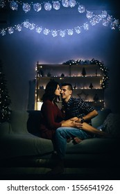 photo under a film photograph with grain happy, couple in love in the dark, evening on the couch, dark background, christmas tree lights. Christmas evening. New Year. hug and kiss.